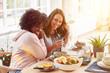 canvas print picture - Zwei glückliche Frauen essen Frühstück in Küche