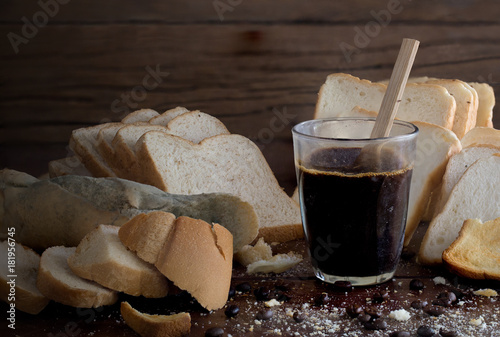 Valokuva  Rotten breads and rancid coffee on old  brown wooden table in dim light room