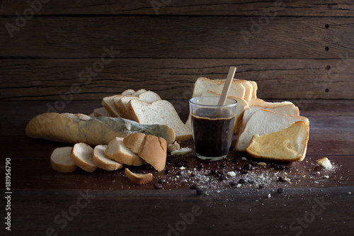 Valokuvatapetti Rotten breads and rancid coffee on old  brown wooden table in dim light room