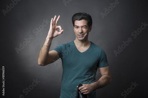 Uomo moro con capelli neri , maglietta verde e giacca in pelle in mano fa il seg Canvas Print