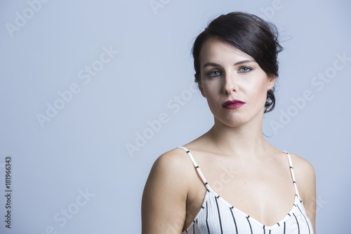 Fotografie, Obraz  Ragazza vestita con abito bianco a righe nere con bretelline , ci guarda seria -
