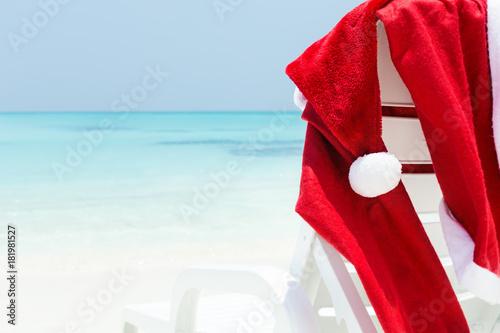 Staande foto Dragen Santa Claus wear hanging on sun lounger