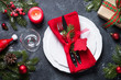 Christmas table setting. Plate, cutlery, present and decorations on dark. Top view,