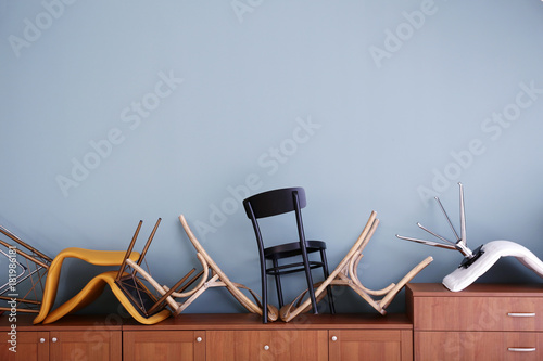 La pose en embrasure Aeroport Chairs piled on chest of drawers against light wall