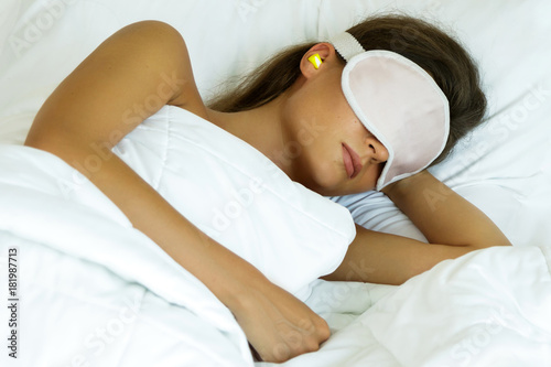 Fotografie, Obraz  Woman is wearing eye mask and using earplugs