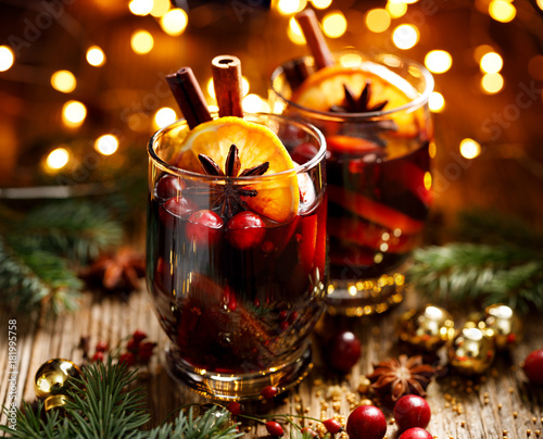Christmas mulled red wine with spices and fruits on a wooden rustic table. Traditional hot drink at Christmas time