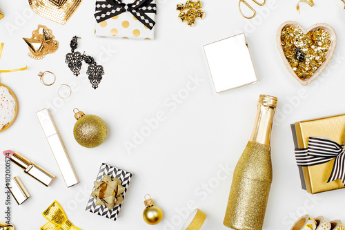 Photo  Flat Lay Christmas or Party Background with Gift boxes, pineapple, Champagne bottle, Bows, Decorations and in Gold colors