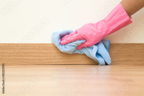 Employee hand in rubber protective glove with micro fiber cloth wiping a baseboard on the floor from dust at the wall Canvas Print
