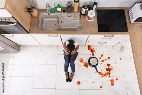 Fotografering  Woman Sitting On Kitchen Floor With Spilled Food