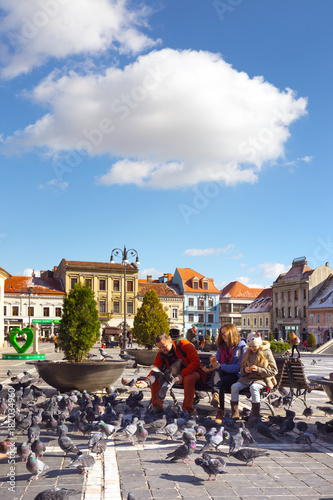 family feeding pigeons on a main square of romanian town Brasov