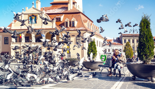 children feeding pigeons on a main square of romanian town Brasov