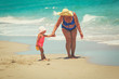grandmother and little granddaughter go swim on beach
