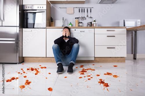 Man Sitting On Kitchen Floor With Spilled Food Billede på lærred