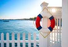 A Beautiful White Wooden Fence And A Marine Lifebuoy On A Background Of Blue Sea Of Sky And Coast. Template For Sea Travel And Vacations, Place For Text.