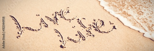 Photo  Live life written text on sand