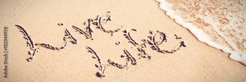 Fototapeta Live life written text on sand