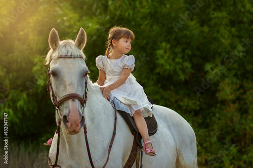 the little girl sits on a horse astride Wallpaper Mural