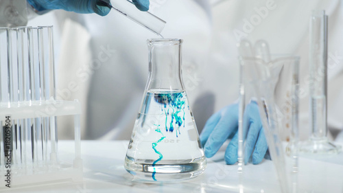Fototapeta Chemist pouring substance into conical flask with liquid, chemical experiment obraz
