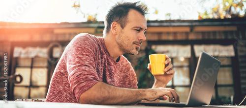 Fototapeta Men drinking coffee and using laptop at backyard patio obraz