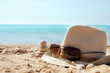 Pyramid of stones to the left of the hat with sunglasses on the sand against the blue sea
