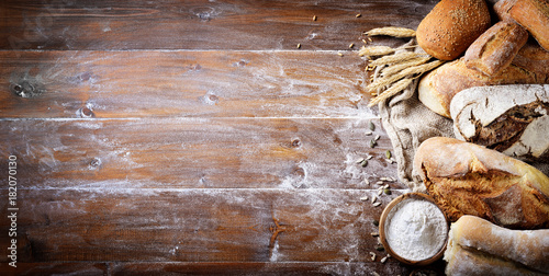 Assorted bread on wood background. Top view with space for text