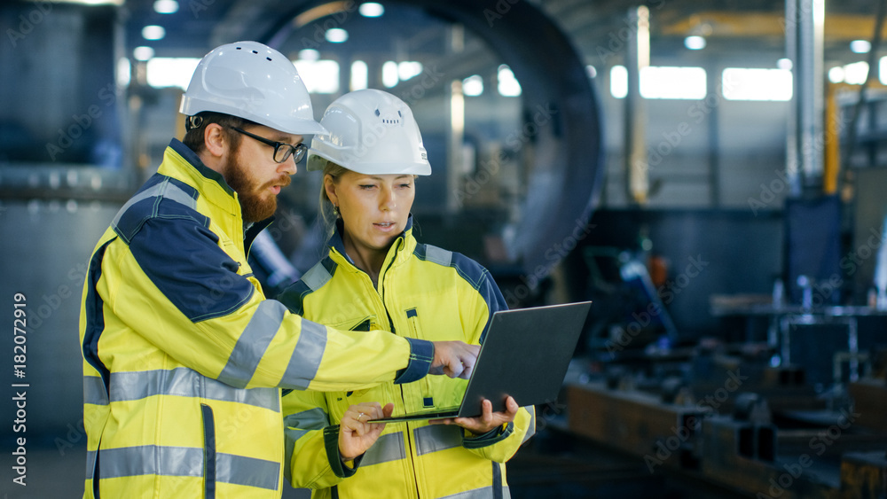 Fototapety, obrazy: Male and Female Industrial Engineers in Hard Hats Discuss New Project while Using Laptop. They Make Showing Gestures.They Work in a Heavy Industry Manufacturing Factory.