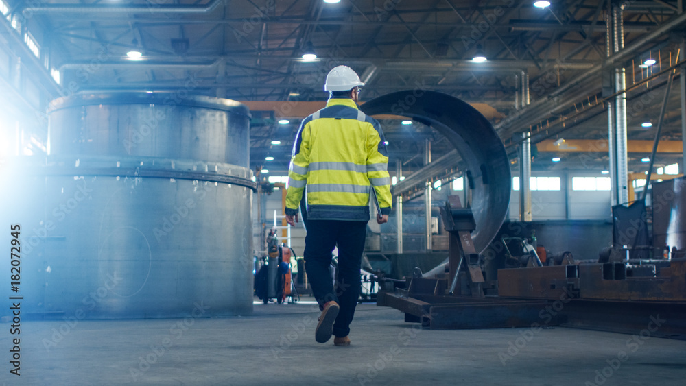 Fototapety, obrazy: Industrial Engineer in Hard Hat Wearing Safety Jacket Walks Through Heavy Industry Manufacturing Factory with Various Metalworking Processes.