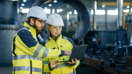 Male and Female Industrial Engineers in Hard Hats Discuss New Project while Using Laptop. They Make Showing Gestures.They Work in a Heavy Industry Manufacturing Factory.