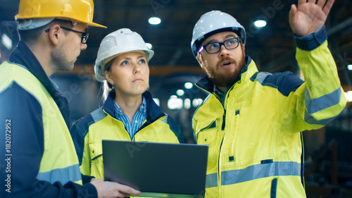 Male and Female Industrial Engineers Talk with Factory Worker while Using Laptop. They Work at the Heavy Industry Manufacturing Facility.