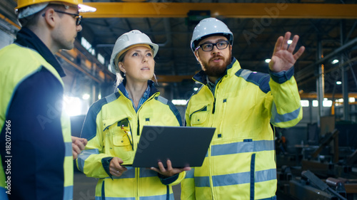 Fotografiet  Male and Female Industrial Engineers Talk with Factory Worker while Using Laptop