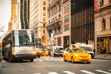 Generic New York City street scene with taxi's buses, cars at intersection and unrecognizable people in typical upscale district