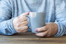 Hands Of An Elderly Woman Holding A Cup Of Hot Tea