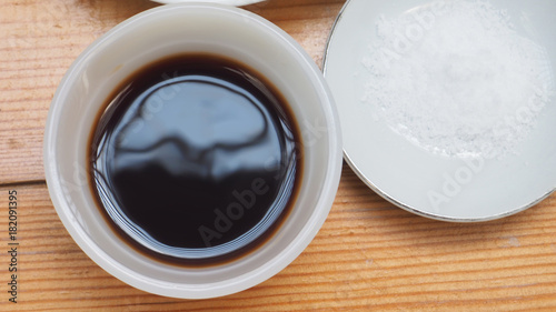 Soy sauce and salt in ceramic cup and plate top view
