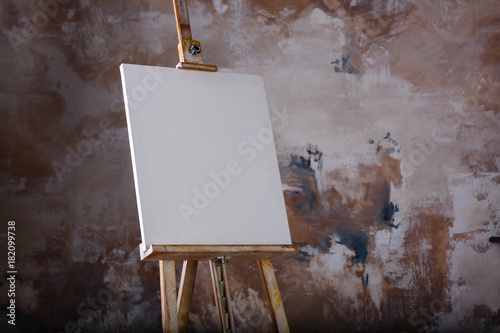 White empty artistic canvas on an easel for drawing images by an artist on a gra Wallpaper Mural