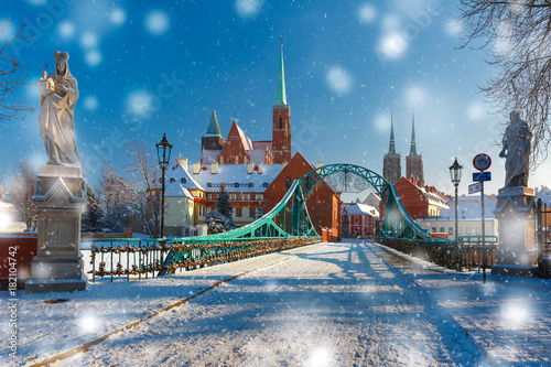 Tumski Bridge and Island with Cathedral of St. John and church of the Holy Cross and St. Bartholomew in the snowy overcast winter day in Wroclaw, Poland