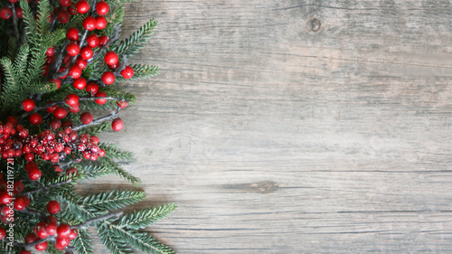 Foto  Holiday Evergreen Branches and Berries Over Rustic Wood Background