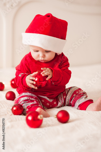 75cbbfbad Cute baby 1 year old wearing res santa claus suit and hat sitting in bed  holding Christmas ball close up. Holiday season. Childhood.
