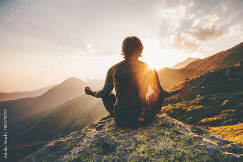 Staande foto School de yoga Man meditating yoga at sunset mountains Travel Lifestyle relaxation emotional concept adventure summer vacations outdoor harmony with nature
