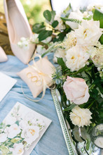 Gift, Engagement, Valentine Concept. On The Sky Blue Draping There Is Dazzling Tray With Great Bunch Of Marvelous Roses On It, Painting Of Flowers, Pink Pillows With Rings And Ladies Shoes