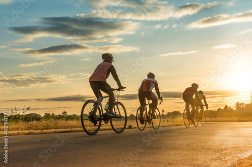 Slika na platnu Group of  men ride  bicycles at sunset with sunbeam over silhouette trees background