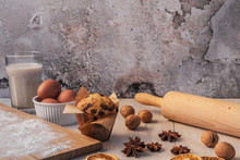 White Wooden Table On A Background Of Empty Concrete Wall With Glass Of Milk, Bamboo Board With Flour, Chocolate Muffin, Walnuts, Dried Orange, Anise And Roll