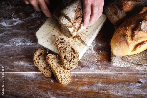 Obraz na plátně Hands cutting rye bread on a wooden brown board
