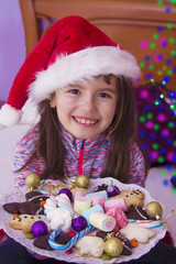 girl with assortment of cookies and christmas candy with christmas lights
