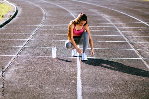 Foto op Plexiglas F1 Woman tying lace on her sneakers on a running stadium