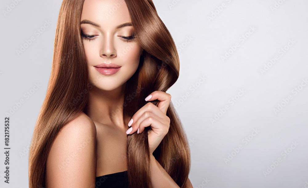 Fototapeta Beautiful brunette girl with long straight smooth hair . A woman with healthy straight hairstyle