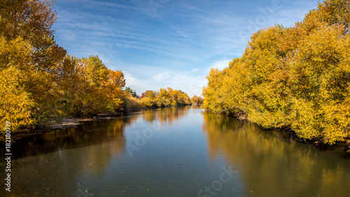 Fall trees line a river in Boise Idaho with blue sky