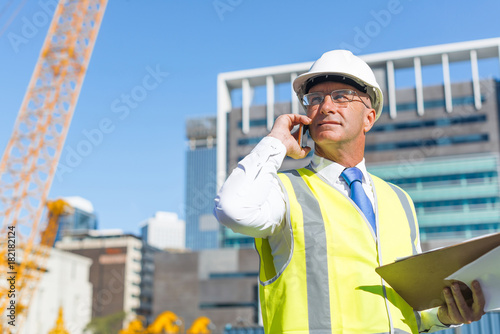 Photo  Man architector outdoor at construction area having mobile conversation