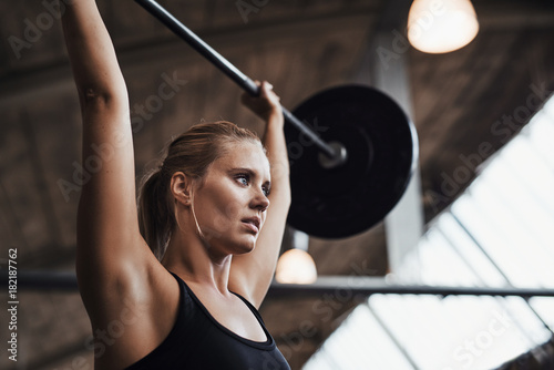 Young woman lifting weights over her head in a gym Tapéta, Fotótapéta