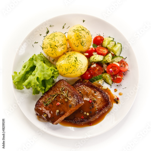 Grilled steak with vegetables on white background