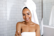 Portrait Of An Attractive Young Woman In Her Bathroom At Home, Wrapped A Towel Around Head